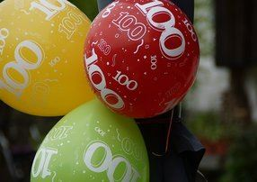 3 celebration balloons--green, yellow, red with number 100 written on them